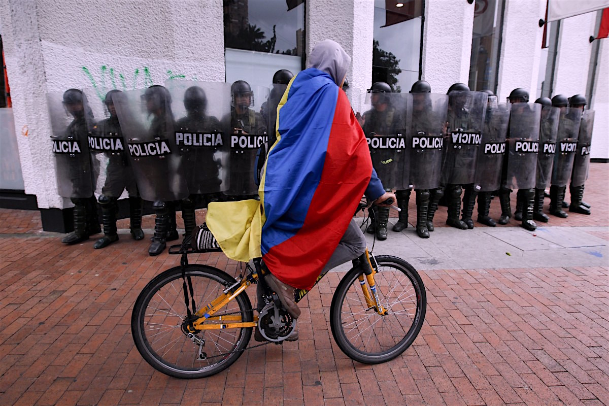 A demonstrator wrapped in a Colombian flag rides past riot police during protests in support of protesting farmers in Bogota, Colombia, Thursday, Aug. 29, 2013. Students marched in support of farmers who have been blockading highways for more than 10 days for an assortment of demands that include reduced gasoline prices, increased subsidies and the cancellation of free trade agreements. (AP Photo/Fernando Vergara)
