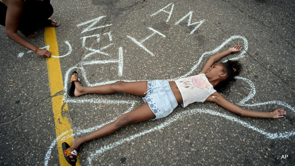 Tia Williams, left, and her daughter Aissa create a display on the street outside the Minnesota governor's official residence Thursday, July 7, 2016, in St. Paul, Minn., as people gathered to protest the shooting death of Philando Castile by police. (Richard Tsong-Taatarii/Star Tribune via AP)