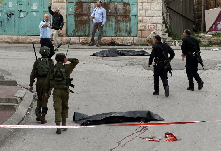 EDITORS NOTE: Graphic content / Israeli soldiers and police surround the bodies of two Palestinians who were killed after wounding an Israeli soldier in a knife attack before being shot dead by troops, an army spokeswoman said, at the entrance to the heavily guarded Jewish settler enclave of Tal Rumeda in the city centre of the West Bank town of Hebron on March 24, 2016. / AFP / HAZEM BADER