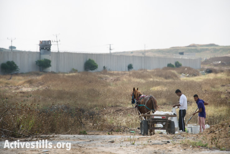 "Palestinian workers salvage building materials near Erez Crossing at Gaza's northern border, Beit Hanoun, May 11, 2014. Human rights organizations have documented dozens of cases of Israeli army gunfire at persons who posed no threat and were well outside the 300-meter so-called ""no-go zone"" imposed by the Israeli military inside Gaza's borders. In many cases, no warning was given before soldiers opened fire."