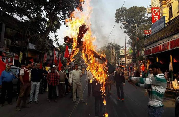 indian men buring an effigy during protests