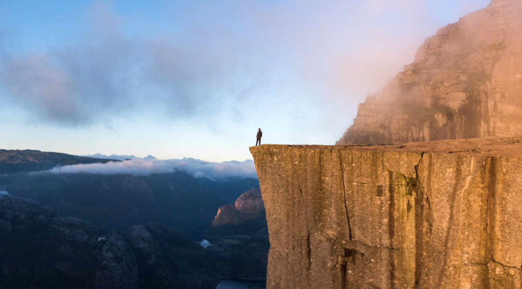 Human standing on the edge of a cliff on a misty morning.