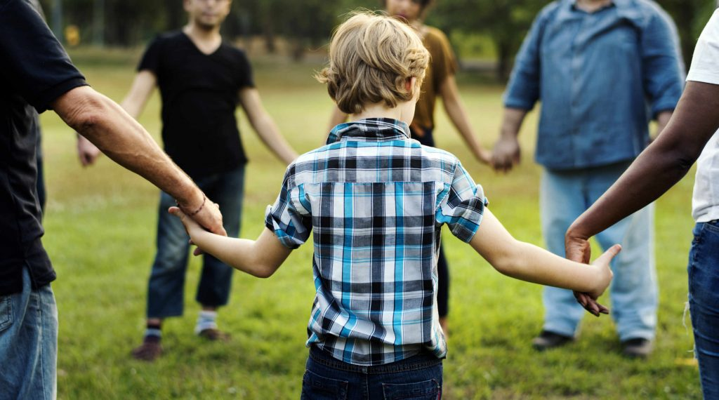 Young boy holding hands with other volunteers in a circle outside in nature.