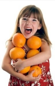 Little girl, arms full of oranges