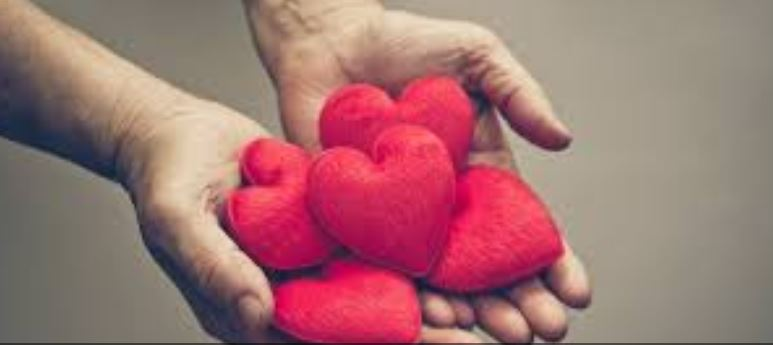 Two hands hold red hearts: compassion
